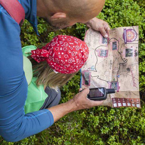 Vater und Tochter blicken auf Schatzkarte - Geocaching Schatzsuche Ötztal